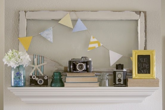a vintage summer mantel with vintage cameras, books, a colorful bunting, blooms and a framed sign