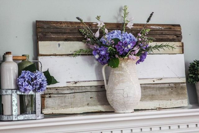a cheerful summer mantel with pallets and bright purple blooms in vases and bottles