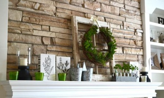 a rustic summer mantel with a greenery wreath and potted greenery, buckets, candle holders and posters