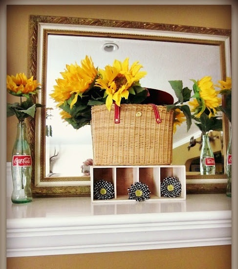 a bright summer mantel with sunflowers, a basket and a large mirror to maximize the light