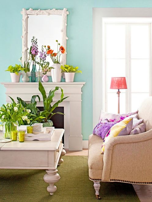 a bright summer mantel with colorful potted blooms and greenery on it and on the coffee table