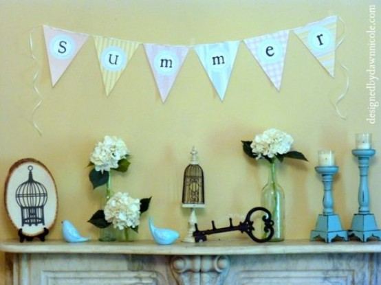 a vintage summer mantel with candles, blooms in vases, a banner, vintage keys and cage decor