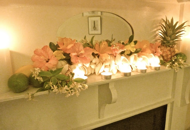 a tropical summer mantel with blush blooms, tropical fruits and candles