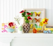 a colorful and bright summer mantel with blooms, vases, bird figurines and bright wrapped gifts