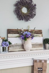 a rustic summer mantel with a lavender wreath, a pallet and purple blooms in vases and jars