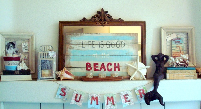 a beachy summer mantel with a pallet sign, framed signs, banners, seashells and starfish