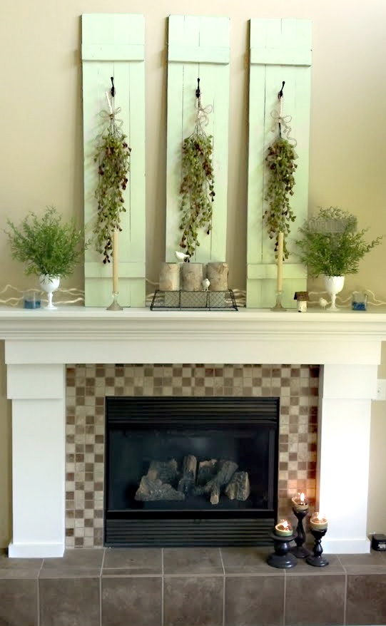 a green summer mantel with green planks with greenery cascading, potted greenery, planters and candles