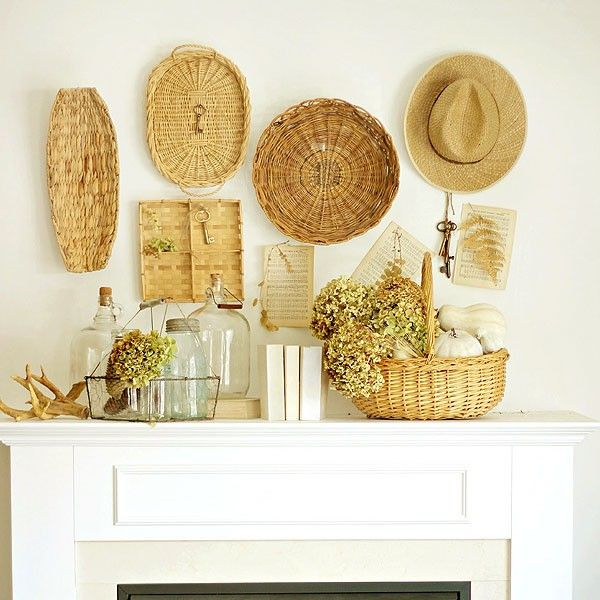 a cozy summer mantel with decorative baskets and trays, a straw hat, a basket with blooms and glass bottles and vases