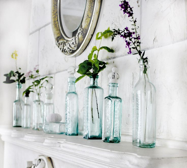 a white mantel with bottles and vases with some blooms and greenery