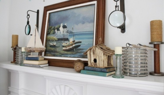 a seaside mantel with a sea artwork, boats, a bird house and nautical lanterns and candles