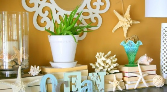 a beachy summer mantel with starfish, seashells, potted greenery and letters