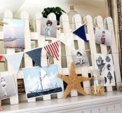a summer mantel with a beachy feel – a white fence, nautical garlands, starfish and family photos from the holiday