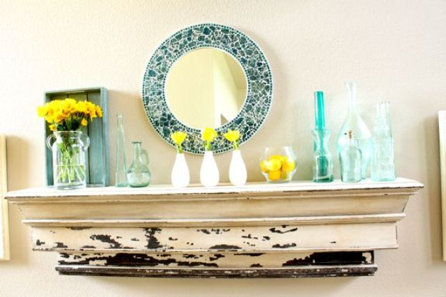 a bright summer mantel done in blue and yellow, with turquoise bottles and vases, yellow blooms and citrus plus a blue mirror