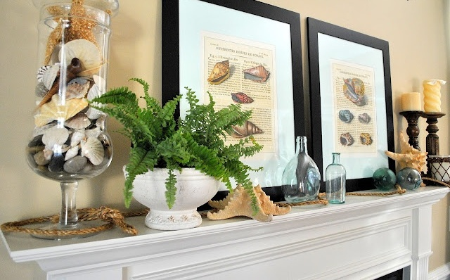 a beachy summer mantel with shell posters, candles, starfish, greenery and a jar with seashells