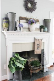 a rustic summer mantel with a shabby pallet, metal buckets, candles, potted greenery and blooms in vases