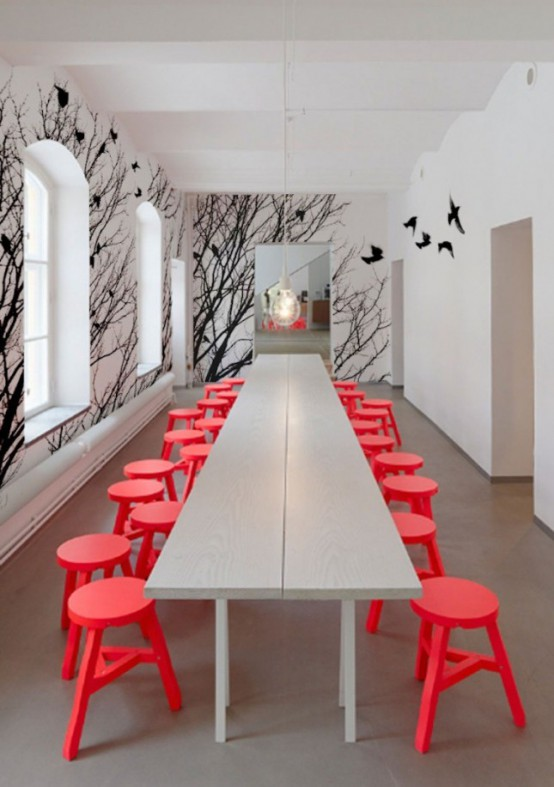 a contemporary dining room in off-white, with red stools and a catchy black birds wall mural to make a statement
