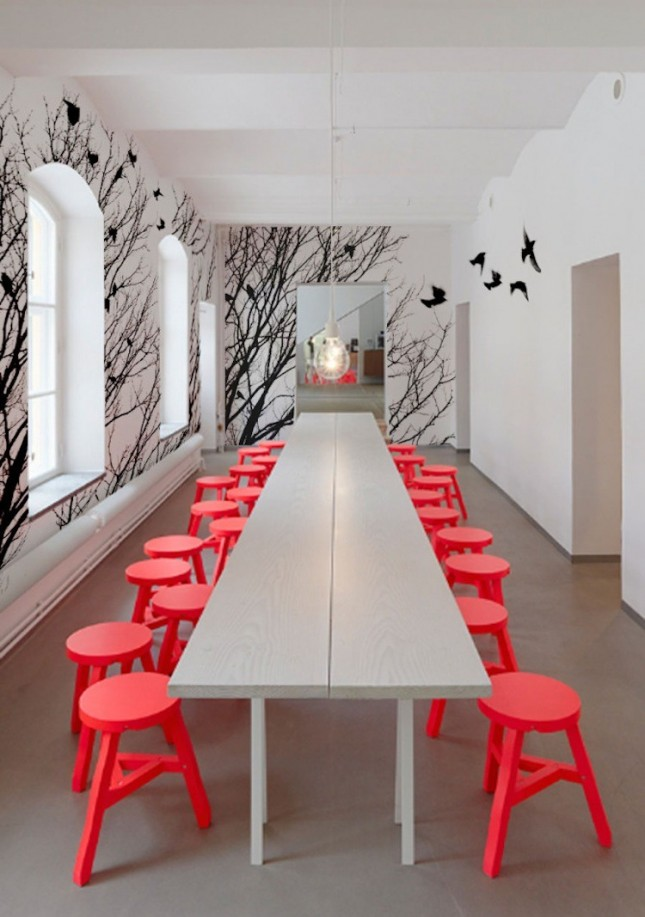 a contemporary dining room in off white, with red stools and a catchy black birds wall mural to make a statement