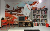 a colorful abstract wall mural matches a boy's bedroom and colorful stuff in it echoes with the mural