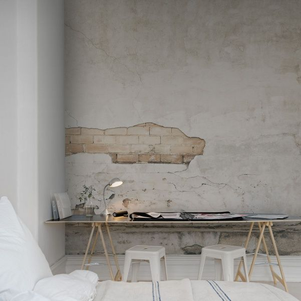 a simple and contemporary space done in neutrals with a catchy wall mural   a textural wall with a brick touch