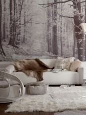 a black and white woodland wall mural matches the color scheme of the space and gives it more eye-catchiness