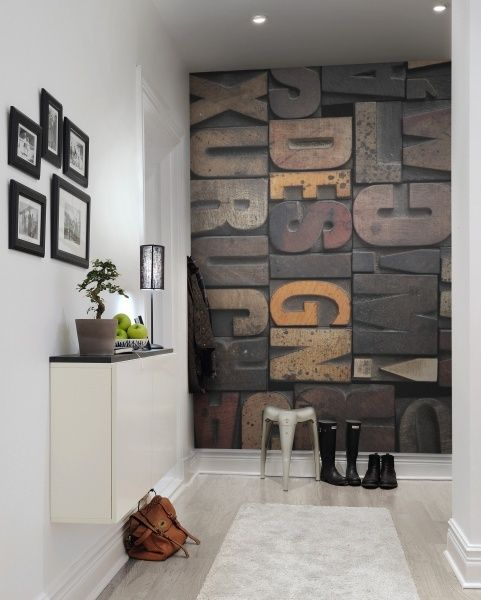 a neutral contemporary entryway with a wooden letter wall mural that adds texture, interest and catchiness