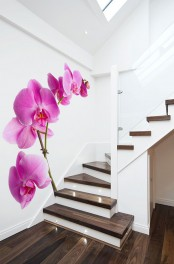 a very laconic space with white walls and a dark stained staircase plus a bright orchid wall mural to add color