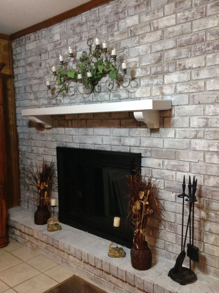 a built in fireplace in a whitewashed brick wall, a mantel with greenery and candles, decorations around