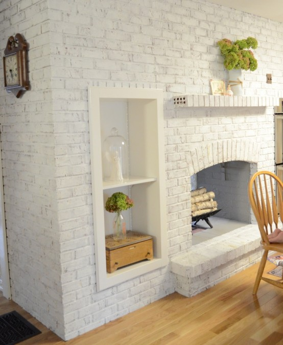 an oversized whitewashed brick non-working fireplace with built-in shelves and potted greenery is a stylish and cozy decoration