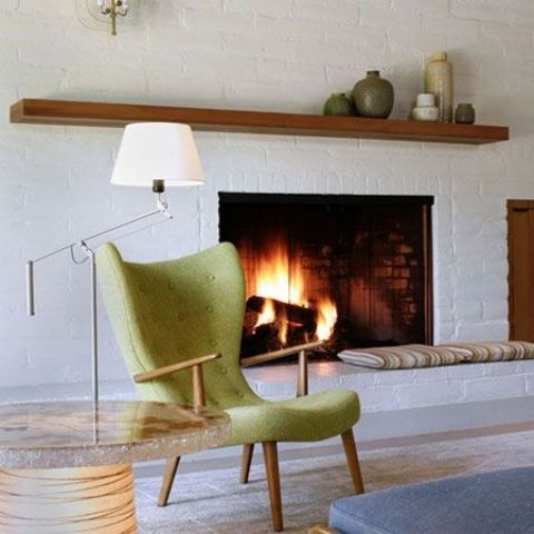 a mid-century modern whitewashed fireplace with a simple mantel and a green chair next to it is stylish and elegant