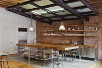 bare brick walls, rustic wood and stainless steel cabinets make this kichen look quite industrial