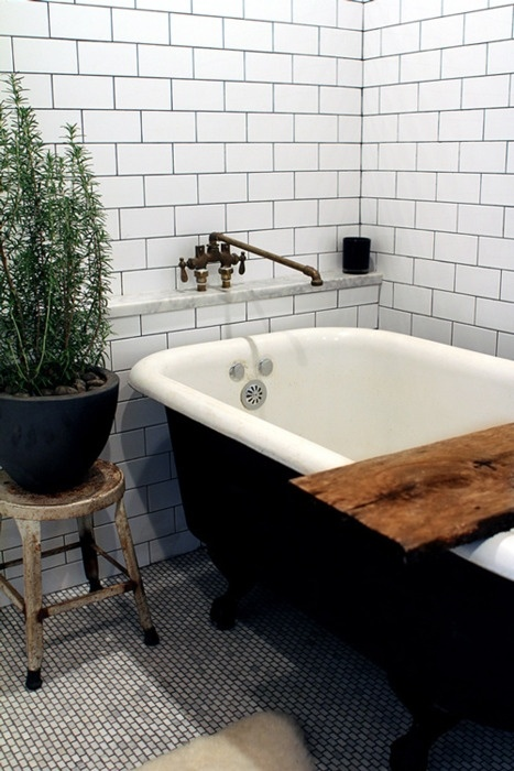 a Scandinavian bathroom with white subway tiles, a black vintage tub and a potted plant for enlivening the space at once