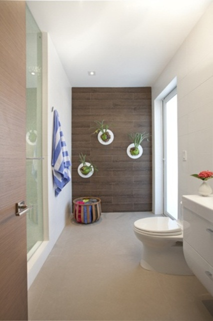 a contemporary bathroom with wall planters with greenery that enliven this space at once and make it fresher