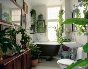 a neutral boho bathroom decorated with lots of potted greenery and succulents here and there feels like an orangery