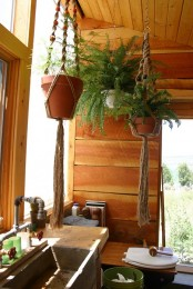 a rustic bathroom clad with warm-stained wood and with greenery in suspended planters that makes it closer to nature