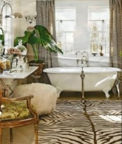 a quriky bathroom with a vintage tub, an animal skin rug, vintage furniture and a potted green plant for a statement