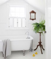 a clean white bathroom with shutters on the window, a vintage tub, a wood frame mirror and a stained plant stand with greenery to refresh the space