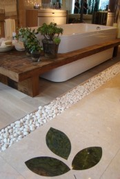 some sheer planters with succulents put on the bench over the tub and pebbles give a real spa feel to the space