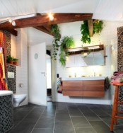a contemporary monochromatic bathroom with stained wooden beams and furniture plus potted greenery placed on the beams, too
