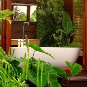a half outdoor and half indoor bathroom clad with wood and with lots of tropical plants for a chic and lively look – completely connected with nature