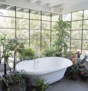 a bathroom with glazed walls and lots of potted plants and greenery around to feel like you are taking a bath outside