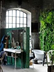 an industrial bathroom done with concrete, with an emerald green tile space divider and a real living wall that refreshes the whole space at once