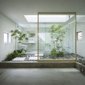 a minimalist white bathroom with a large skylight and trees growing right in the pebbles for a natural look