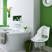 a bold green and white bathroom with a green wall planter with greenery to make the space lively and more nature-inspired
