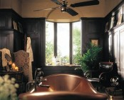 a dark art deco bathroom with black walls, a copper tub and a potted palm tree for a chic and bold look