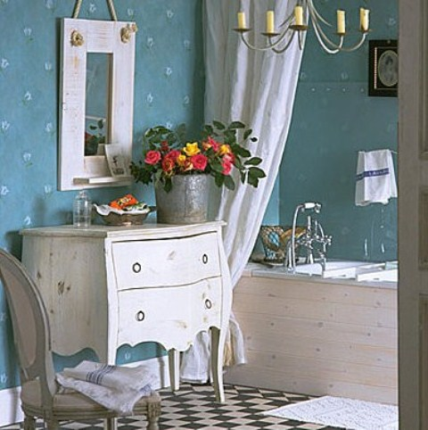 a vintage-inspired bathroom with blue wallpaper walls, refined white furniture and some blooms in a bucket planter for a rustic feel