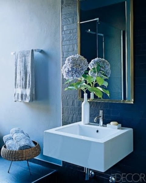accent your modern bathroom with some blooms in a vase or a bottle to make the space lively and chic
