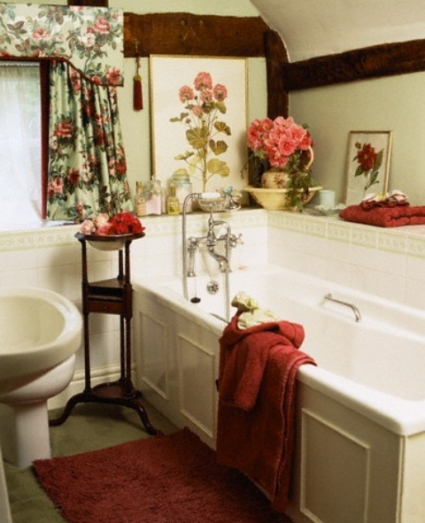 a vintage bathroom with floral artworks, curtains and some blooms in a vase and in a bowl for a sweet feel