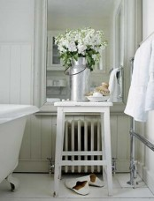a white bathroom with fresh blooms in a metal jar that refresh the space and add a spring feel to it