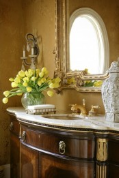 a vintage bathroom with refined furniture and a mirror plus bold blooms in a vase to make it feel fresh and modern