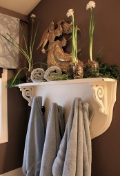 moss and greenery branches and some potted blooms make any bathroom feel cool and refreshed